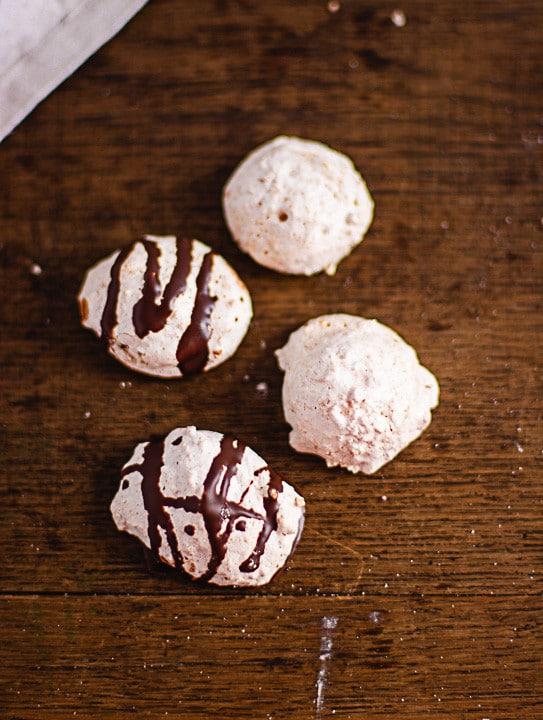 Zwei Kokosmakronen und zwei weitere Kokosmakronen mit Schokolade auf einem Tisch
