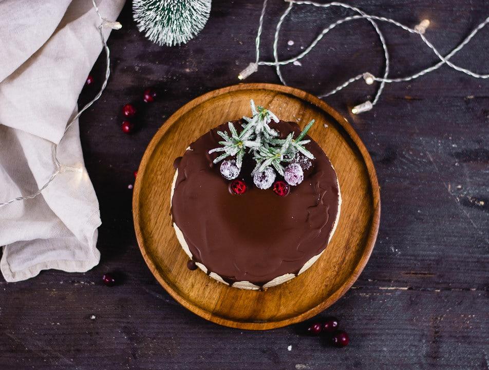 Weihnachtlicher Käsekuchen fotografiert von oben auf einem dunklen, runden Holzteller. Neben dem Teller liegt eine beige Serviette. Der Teller steht auf einer sehr dunklen Tischplatte.