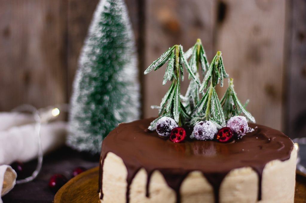 Die Dekoration des weihnachtlichen Käsekuchens besteht aus Rosmarienzweigen, die in Zucker gewälzt werden. Dadurch sehen sie aus wie kleine Tannenbäume. Außerdem liegen drei gezuckerte Cranberries auf dem Kuchen.