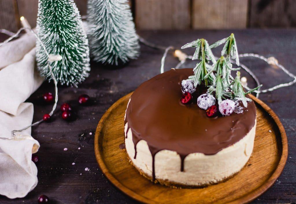 Der fertige weihnachtliche Käsekuchen auf einem runden Holzteller umgeben von weihnachtlicher Dekoration.