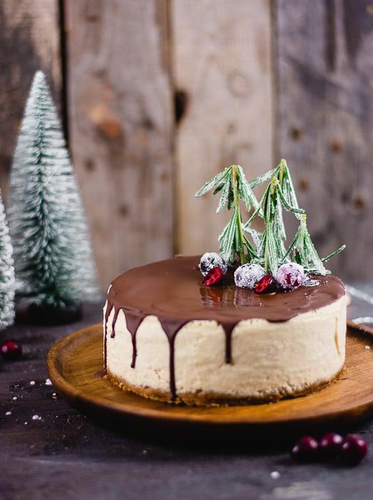 Weihnachtlicher Käsekuchen mit essbarer Dekoration auf Rosmarienzweigen die aussehen wie kleine Tannenbäume und gezuckerten Cranberries.