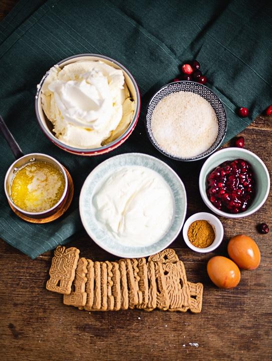 Alle Zutaten, die Du für den weihnachtlichen Käsekuchen benötigst auf einen Blick: Butter und Spekulatius für den Boden. Frischkäse, Griechischer Joghurt, Zucker und Eier für die Creme. Preiselbeermarmelade für die Füllung.