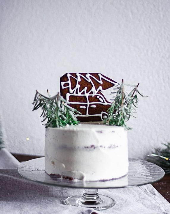 Eine Torte mit Lebkuchenauto und eingeschneiten Chistbäumen aus Rosmarinzweigen und Zucker