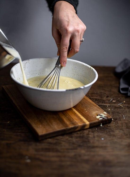 Nach und nach wird die heiße Milch in die Eiermasse für die Vanillesauce eingeführt.