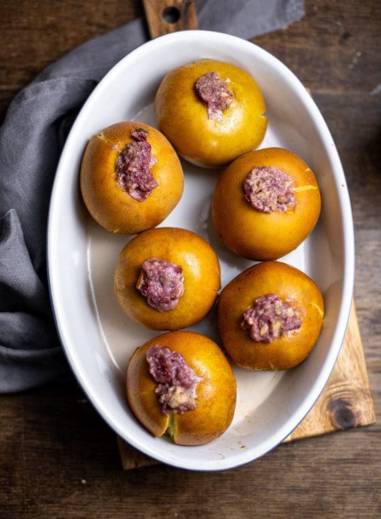 Sechs Bratäpfel stehen in einer weißen, ovalen Auflaufform. Die Bratäpfel sind gebacken, die Schale ist an vielen Stellen leicht aufgesprungen. Durch die enthaltene Preiselbeermarmelade ist die Füllung der Bratäpfel leicht rosa.