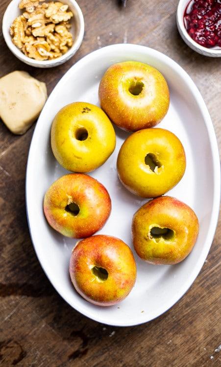 Sechs entkernte Äpfel stehe in einer weißen, ovalen Keramik Auflaufform. Im Hintergrund zu sehen sind die Zutaten für die Füllung, nämlich Marzipan, Preiselbeeren und Walnüsse.