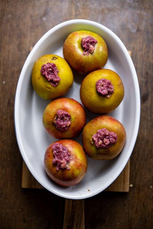 Sechs Bratäpfel, mit Marizpan und Preiselbeeren gefüllt steht in einer ovalen, weißen Keramik Form. Die Bratäpfel sind noch ungebacken.