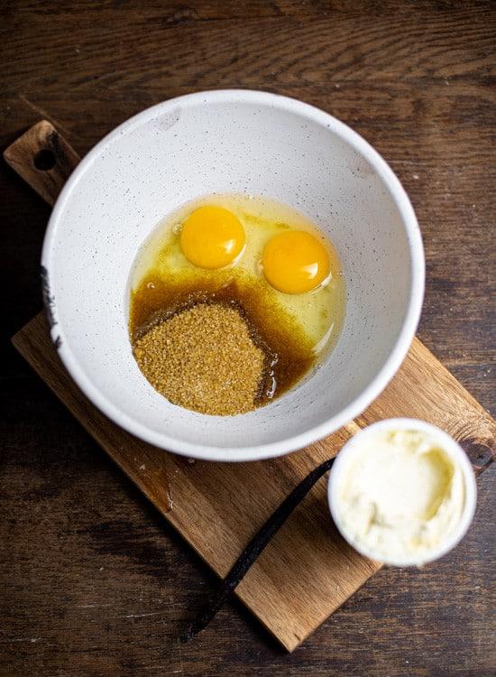 Für die Vanillesauce sind folgende Zutaten nötig: Eier, Zucker, Speisestärke, Vanilleschote und Schlagsahne. Die Eier und der Zucker befinden sich in einer weißen Schüssel. Die Vanilleschote liegt neben der Schüssel. Die Sahne steht ebenfalls neben der Schüssel und befindet sich noch im Becher.