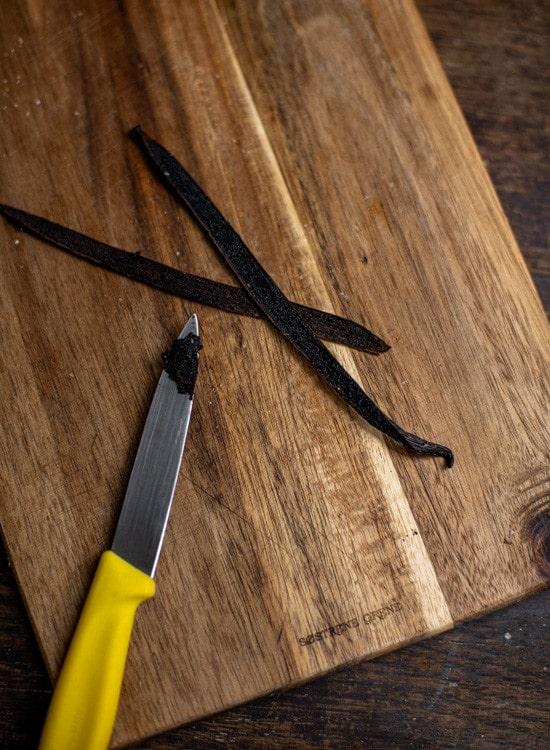 Zur Verwendung der Vanilleschote wird deren Mark ausgekratzt. Die Vanillschote liegt längs halbiert auf einem dunklen Holzbrett. Ein kleines Messer mit gelbem Griff liegt mit auf dem Brettchen. An der Spitze des Messers befindet sich das ausgekratzte Mark der Vanilleschote.