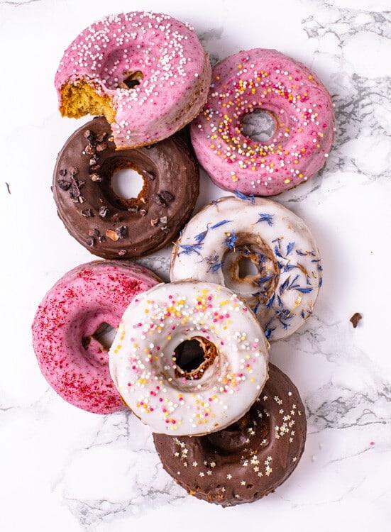 Sieben Donuts aus dem Backofen liegen auf einer Marmorplatte. Ein weiß glasierter Donut mit bunten Streuseln liegt auf drei anderen Donuts. Ein rosa glasierter Donut mit weißen Zuckerstreuseln darauf ist angebissen.