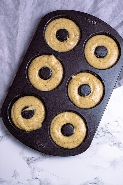 Damit der die Donuts nach dem Backen auf hübsch aussehen darf der Teig maximal 2 mm unterhalb der Form enden.