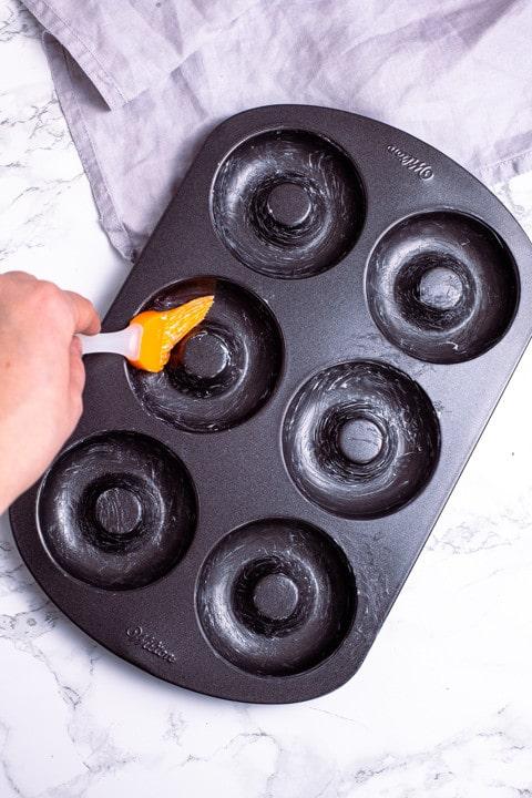 Die Donutform, ein dunkelgraues Blech mit 6 Donutmulden darin wird vor dem Backen großzügig mit Butter ausgepinselt.