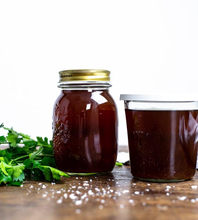 Selbst gemachte Gemüsebrühe in zwei Gläser abgefüllt stehen auf einem Holztisch. Im Hintergrund liegt etwas glatte Petersilie und etwas Salz liegt auf dem Tisch.