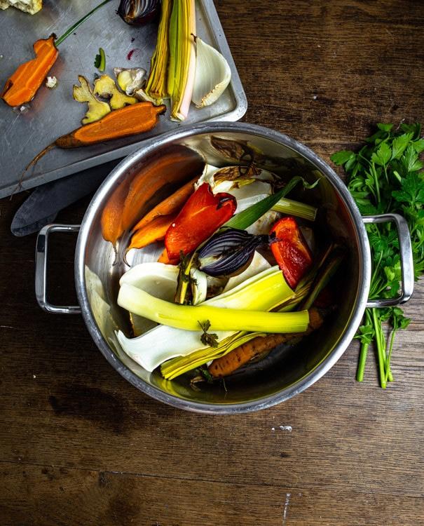 Auch das restliche geröstete Gemüse kommt mit in den Topf. Im Topf befinden sich nun Paprika, eine halbe, rote Zwiebel, Karoffen und Co. Der Topf steht auf einem alten Holztisch. Außerdem ist das Blech mit den restlichen gerösteten Gemüsestücken zu sehen. Petersilie und getrocknete Tomate liegen neben dem Topf auf dem Tisch.