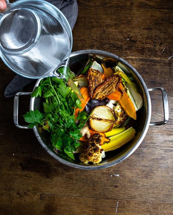 Petersilie und getrocknete Tomaten liegen nun auch im Topf. Mit einer großen Karaffe wird Wasser aufgegossen.