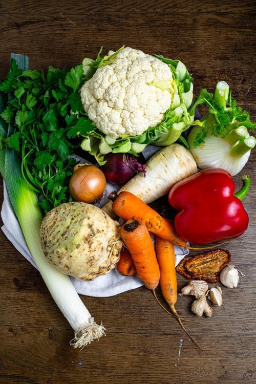 Gemüse für die Gemüsebrühe liegt auf dem Tisch. Ein Blumenkohl, zwei Zwiebeln, eine Pastinake, ein Fenchel, eine rote Paprika, eine Sellerienknolle, drei Karotten, Lauch, getrocknete Tomaten sowie Knoblauch und Ingwer kommen in die Gemüsebrühe.