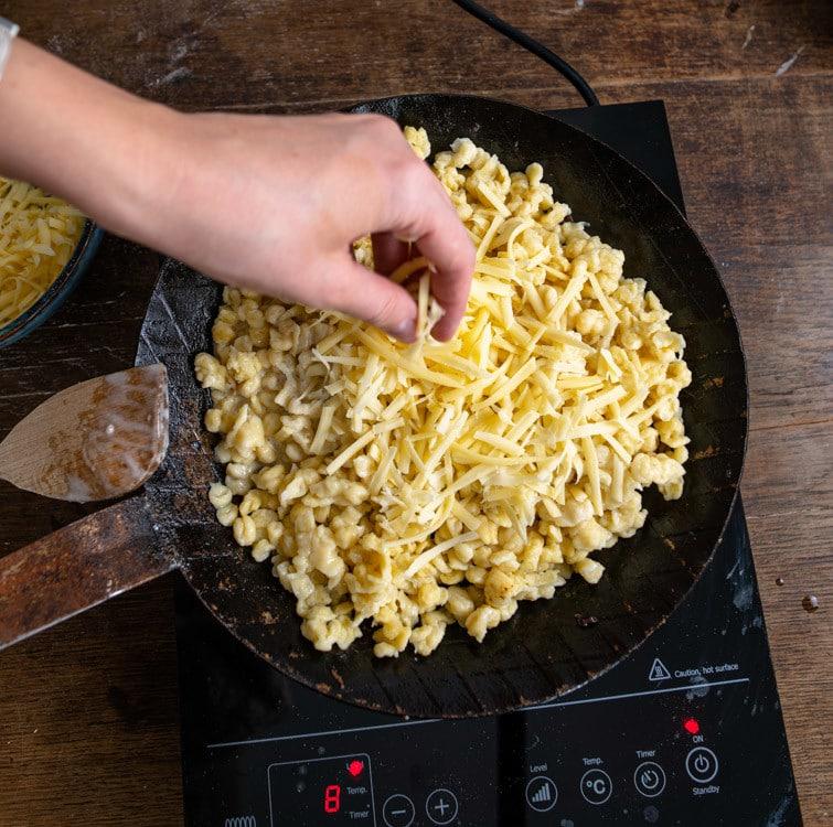 Die Käsespätzle können auch in der Pfanne zu bereitet werden. Dafür werden Spätzle und Käse in eine Gusseisenpfanne gebeben. Zu sehen ist auch der Kochlöffel mit dem in der Pfanne umgerührt wird und die Kochplatte auf der die Pfanne steht.