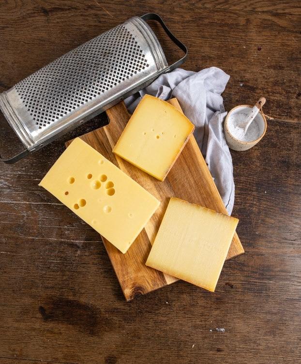 Eine Auswahl von drei Käsen liegt auf einem Brett auf dem Tisch. Zu sehen sind Appenzeller, Le Gruyere und Emmentaler. Außerdem mit im Bild ist eine Reibe und ein Schälchen mit Salz.