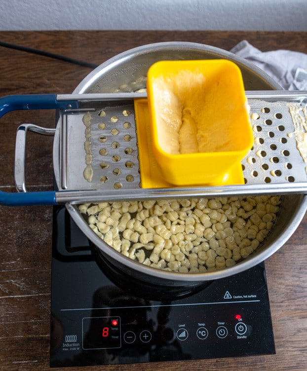 Die Spätzle werden mit Hilfe eines Spätzlehobels hergestellt. Dieser liegt über einem großen Topf mit kochendem Wasser. Im Topf schwimmen bereits fertige Spätzle.