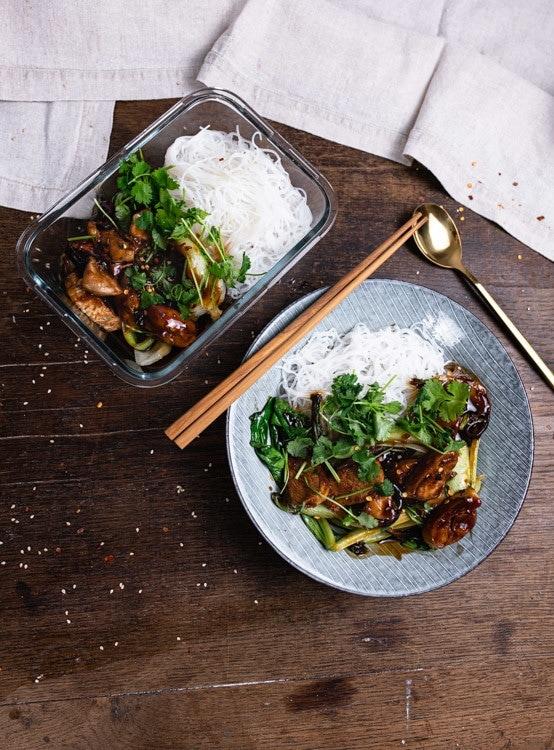 Zwei Portionen Reisnudeln mit Hähnchen und Pak Choi in Honig Soja Marinade stehen auf dem Tisch. Eine Portion befindet sich in einem tiefen, blauen Teller. Die andere Portione befindet sich in einer rechteckigen Glasschale.