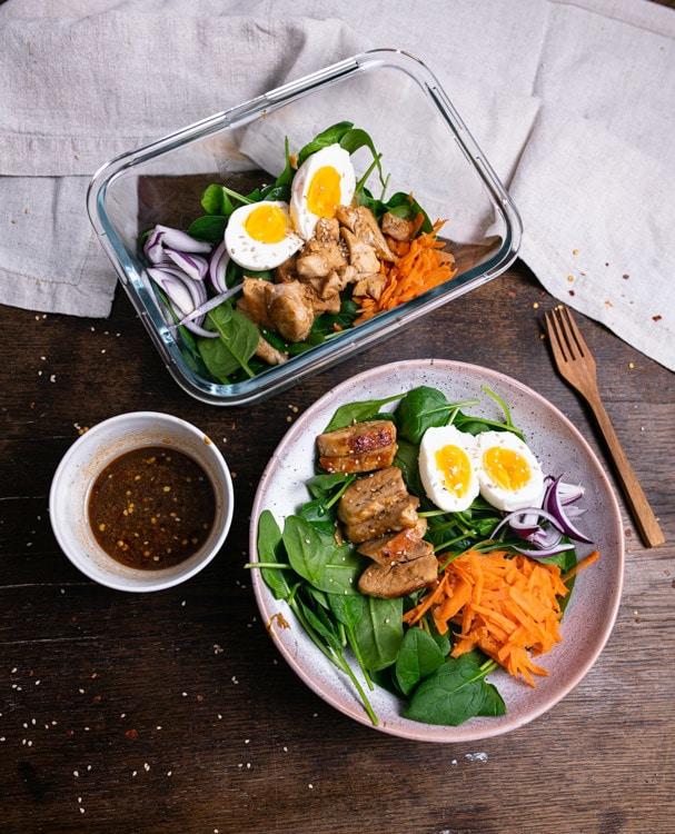 Zwei Portionen Spinatsalat mit Hähnchen, Karotte und Ei und ein Schälchen mit Dressing stehen auf einem alten Holztisch. Eine Portion befindet sich in einem rechteckigen Glasgefäß. Die zweite Portion befindet sich in einem beigen, hand getöpferten Teller.