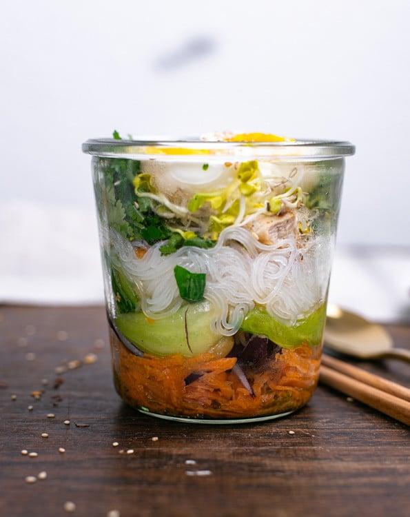 Die Ramen To Go Befindet sich zubereitet in eine hohen Glasgefäß. Die Zutaten sind in Schichten in das Gefäß gelegt. Die einzelnen Schichten sind gut zu erkennen. Sie beginnen mit Misopaste und Gemüsebrühe, gefolgt von Karotten und enden mit Koriander, Sprossen ind Eier.