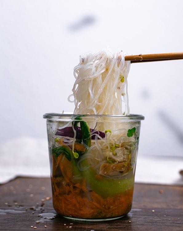 Die Ramen To Go wurde mit heißem Wasser aufgegossen. Mit Essstäbchen aus Holz werden die Reisnudeln aus dem Gefäß gehoben.