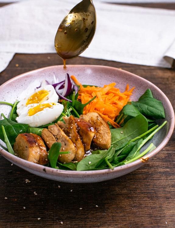 In einer handgetöpferten Schüssel ist der Spinatsalat des Meal Prep angerichtet. Mit einem goldenen Esslöffel wird Dressing über das Hähnchen und die Eier geträufelt, die auf dem Spinatsalat liegen.