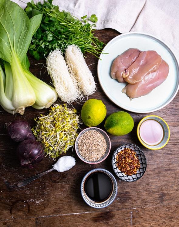 Die Zutaten für das Meal Prep Rezept Reisnudeln mit Hähnchen und Pak Choi ind Honig Soja Marinade stehen auf einem alten Holztisch. Von oben nach unten und links nach rechts sind das Hühnerbrüste, Koriander, Reisnudeln, Pak Choi, Honig, Limetten, Sesam, Sojasprossen, Zwiebeln, Chiliflocken, Pflanzenöl und Sojasauce