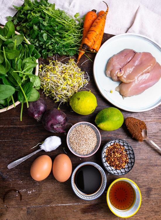 Die Zutaten für das Meal Prep Rezept Spinatsalat mit Hähnerbrust und Karotte stehen auf einem alten Holztisch. Von oben nach unten und links nach rechts sind das Hühnerbrüste, Karotten, Koriander, Babyspinat, Misopaste, Limetten, Sojasprussen, Chili, Sesam, Zwiebeln, Sojasauce, Eier, Pflanzenöl und Honig