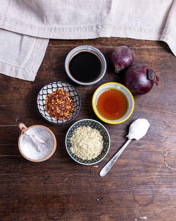 Die Zutaten, die Du aus der Vorratskammer benötigst stehen auf einem Tisch. Von oben nach unten und links nach rechts sind das Zwiebeln, Sojasauce, Honig, Chiliflocken, Pflanzenöl, Gemüsebrühe und Salz.