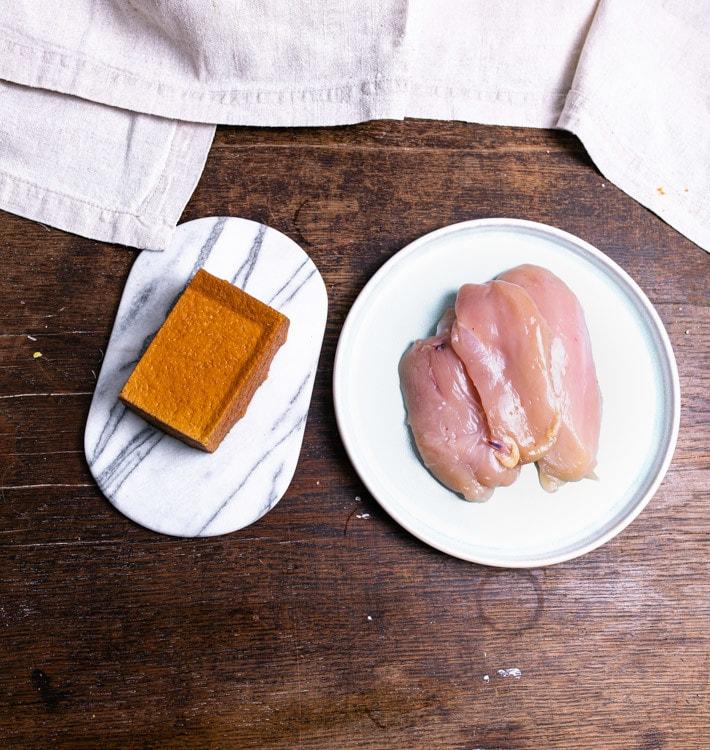 Auf einem alten Holztisch liegen rechts im Bild drei Hühnerbrüste auf einem weißen, runden Teller. Links daneben liegt ein Stück Räuchertofu auf einer ovalen, weißen Marmorplatte.