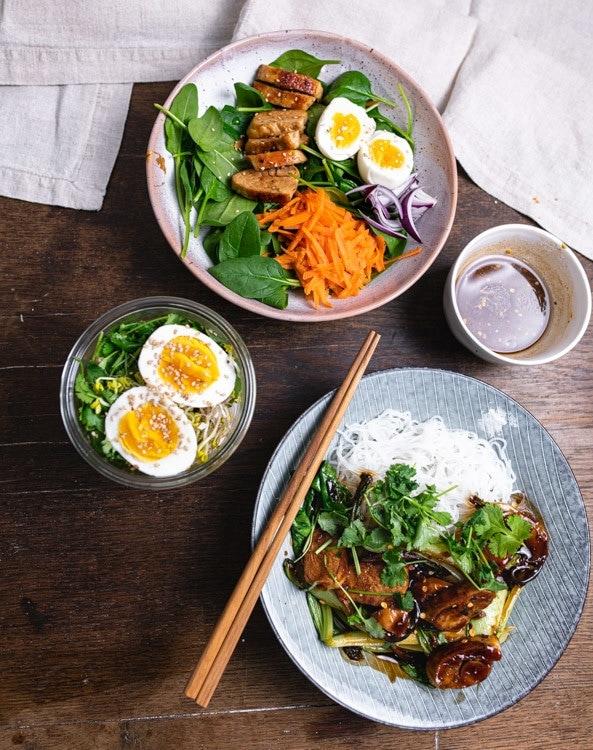 Meap Prep mit 10 Zutaten für drei Gerichte. Die drei Gerichte stehen auf einem Holztisch. Am oberen Rand ist der Spinatsalat mit Karotten, roter Zwiebel, Ei und Hähnchen zu sehen. In der Mitte steht die Ramen Suppe mit einem gekochten Ei und Korian der on Top. Rechts daneben ist das Dressing für den Salat zu sehen. Unten im Bild ist ein blauer, tiefer Teller mit mit Reisnudeln, Hähnchen und Pak Choi ind Honig Soja Marinade mit frischen Koriander.