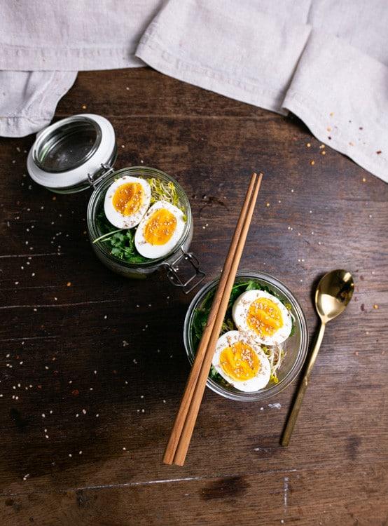 Zwei Portionen Ramen To Go stehen auf einem dunklen, alten Holztisch. Beide Portionen befinden sich in Glasgefäßen. Auf einem Gefäß liegen Essstäbchen aus Holz, neben den Gefäßen liegt ein goldener Esslöffel.
