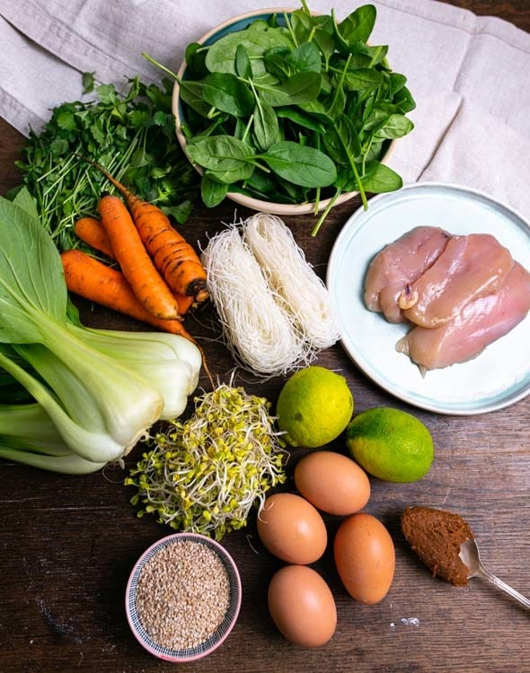 Nur 10 Zutaten müssen für das Meal Prep Rezept eingekauft werden. Diese Zutaten liegen auf einem Tisch. Von oben nach unten un recht nach links sind das Babyspinat, daneben liegt Koriandergrün, Hühnerbrust, Reisnudeln, Karotten, Pak Shoi, Limetten, Sojasprossen, Mispoaste, Eier und Sesam.