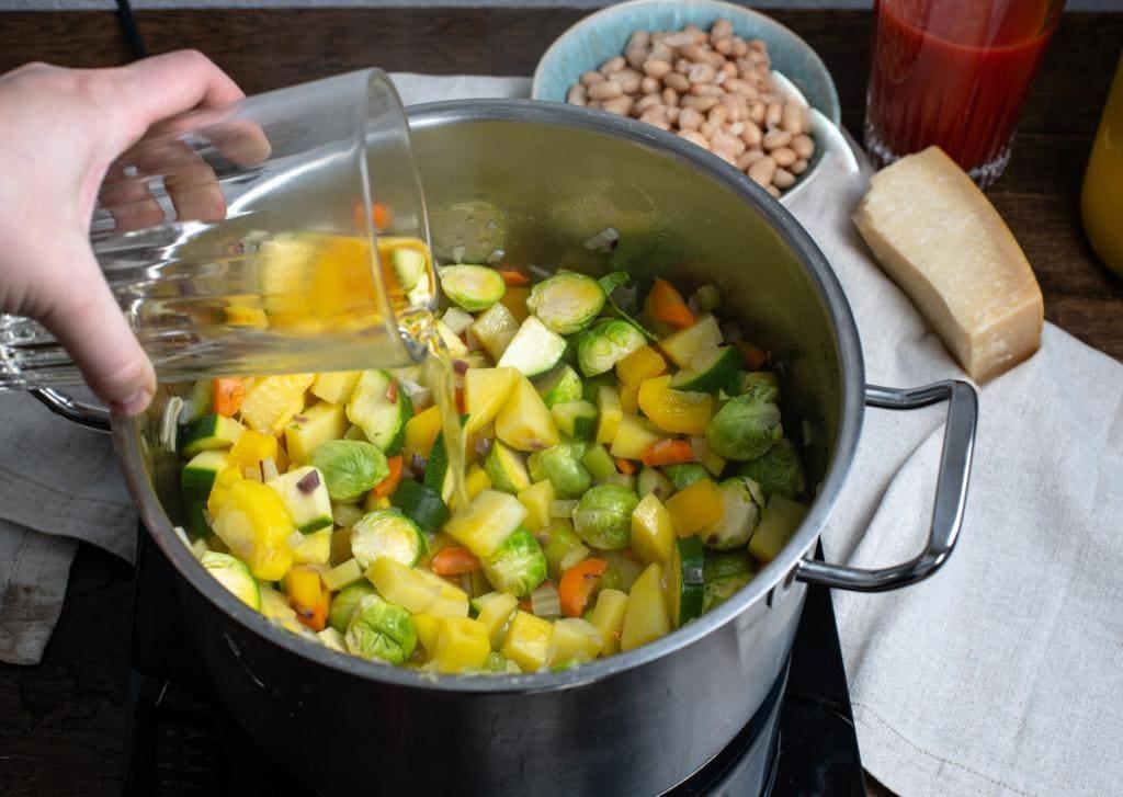 Das Gemüse im Topf wird mit Weißwein aufgegossen.