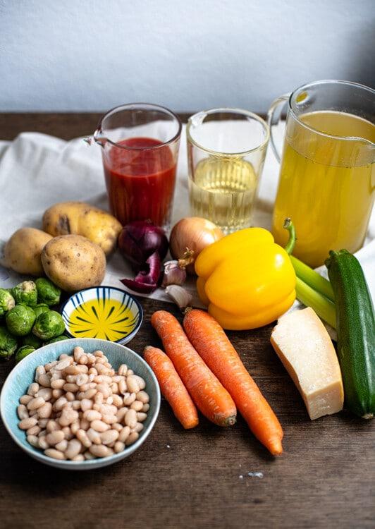 Die Zutaten der Minestrone liegen auf einem alten Holztisch zu sehen ist von links nach rechts und von vorne nach hinten weiße Bohnen, Rosenkohl, Kartoffeln, Karotten, Olivenöl, Zwiebeln, Dosentomaten, eine gelbe Paürika, Weißwein, Parmesan, Zucchini, zwei Stangen Sellerie und und ein Krug mit Gemüsebrühe.