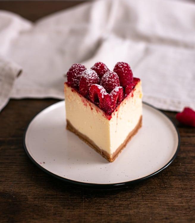 Ein Stück des New York Cheesecake steht auf einem Teller. Man erkennt in der Nahaufnahme deutlich die frischen, saftigen Himbeeren und die cremige, samtige Konsistenz der Creme. Der Boden ist knusprig und besteht aus Keksbröseln.