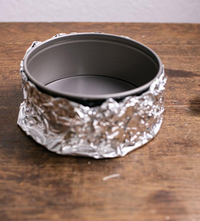 Damit das Backen im Wasserbad gelingt muss die Form mit Alufolie Wasserdicht abgedichtet werden. Die mit Alufolie dicht gemachte Form steht auf diesem Foto auf dem Tisch.