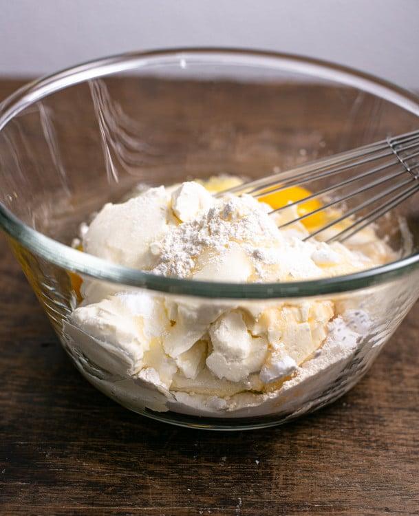 Die Zutaten für die Cheesecake Creme kommen in eine große Rührschüssel. Sie werden mir einem Schneebesen so lange verrührt, bis keine Klümpchen mehr vorhanden sind.