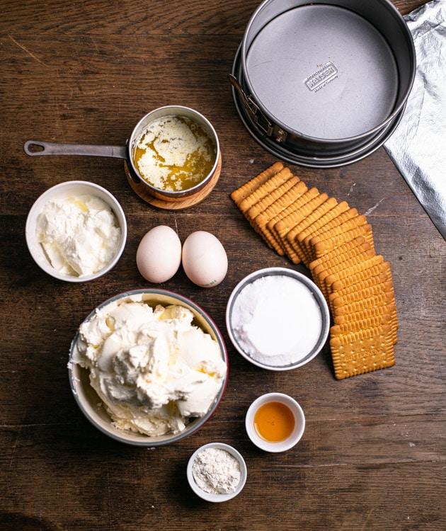 Die Zutaten für den New York Cheesecake liegen auf dem Tisch. Von oben nach unten und rechts nach links sind das: Alufolie, Springform mit 18 cm Durchmesser, geschmolzene Butter, Butterkekse. Eier, Sauerrahm, Zucker, Frischkäse, Vanilleextrakt und Mehl.