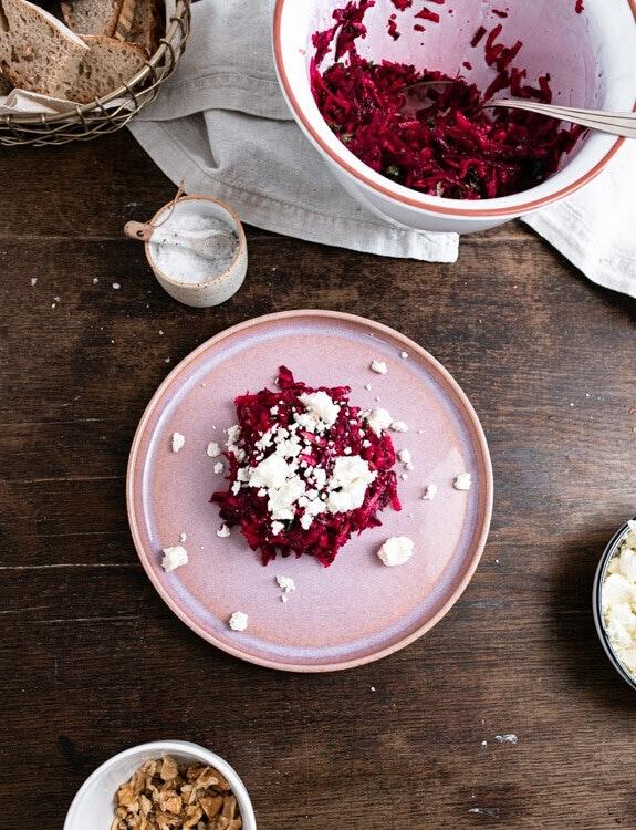 Rote Beete Salat wird auf einem rosa Teller angerichtet. Auf dem und um den Salat herum liegen größere und kleinere Fetakrümel.
