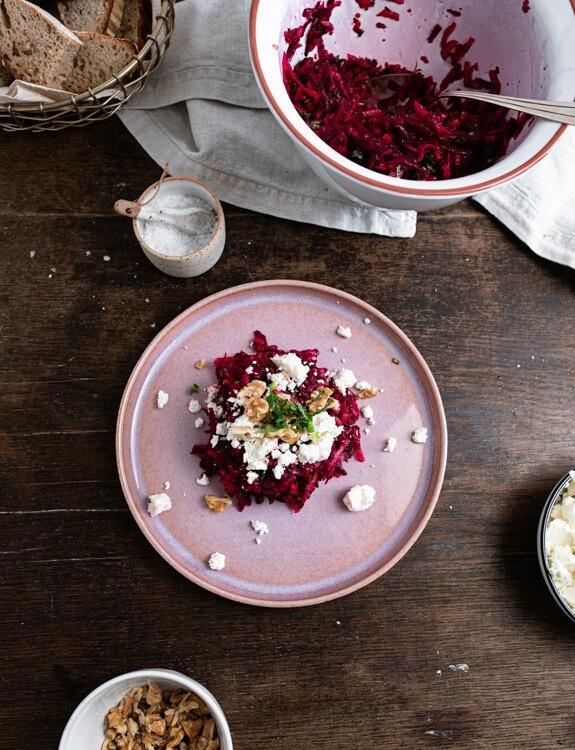 Rote Beete Salat mit Feta, Walnüssen und Minze auf einem rosa Teller angerichtet. Rund um den Teller sieht man weitere Schälchen auf dem Tisch stehen. In einem befindet sich zerkrümelter Feta, in einem anderen gehackte Walnüsse. Die Schüssel mit dem restlichen Salat ist ebenfalls im Hintergrund zu sehen.