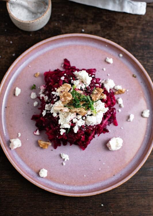 Rote Beete Salat mit Feta, Walnüssen und Minze auf einem rosa Teller angerichtet. Im Hintergrund ist ein Schälchen mit Salz zu sehen.