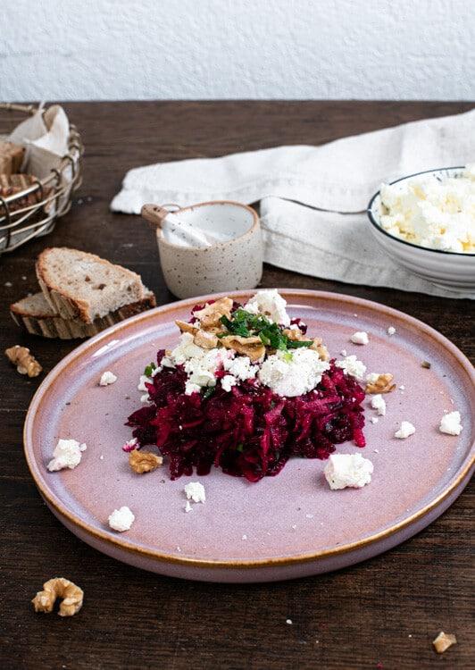 Auf dem Rote Beete Salat liegen einige Fetakrümel. Der Feta wurde zwischen den Fingern grob zerbröselt. Walnüsse und etwas Minze krönen den Salat. Im Hintergrund sind einige Brotscheiten, ein Schälchen mit Salz und eine Schale mit Feta zu sehen.