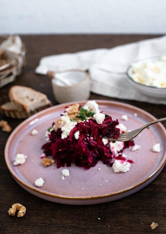 Rote Beete Salat ist auf einem rosa Teller angerichtet. Mit einer silbernen Gabel wurde etwas des Salates aufgegabelt. Die Gabel mit Salat und Fetakrümeln wird in die Kamera gehalten. Der restliche Teller verschwimmt etwas im Hintergrund.