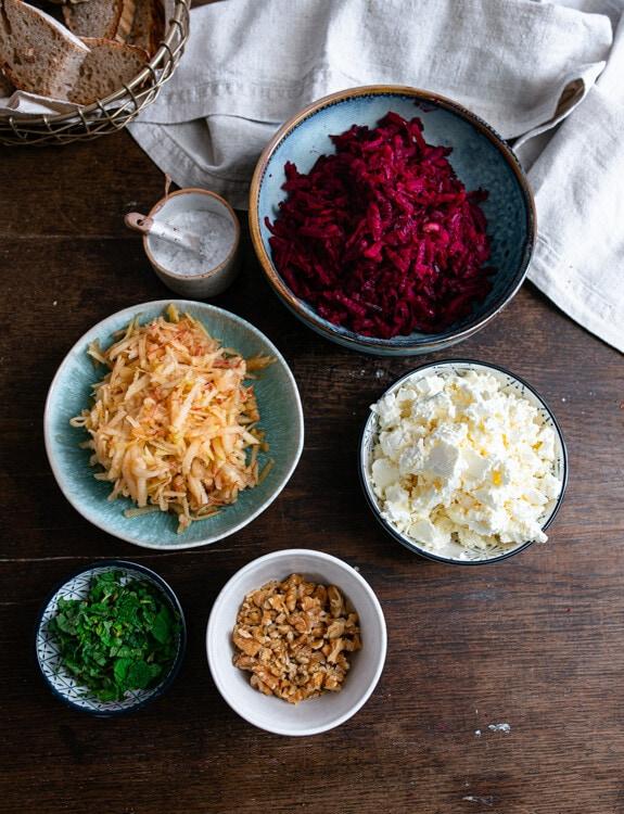 Die Zutaten für den Rote Beete Salat sind auf diesem Foto bereits verarbeitet. Apfel und Rote Beete sind grob geraspelt und liegen jeweils in einer eigenen, blauen Schale. Der Feta ist grob zerbröselt, die Walnüsse sind grob gehackt und die Minze ist in feine Streifen geschnitten.