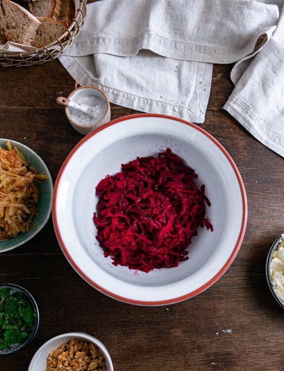 Nun kommen die Zutaten in eine größere Schüssel. Auf diesem Foto befindet sich die geraspelte rote Beete bereits in der weißen Keramikschüssel. Die übrigen Zutaten stehen rund um die Schüssel auf dem Tisch.