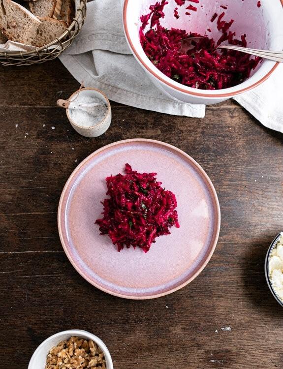 Rote Beete Salat wird auf einem rosa Teller angerichtet. Rund um den Teller herum ist die Schüssel mit den restlichen Salat zu sehen, ein Schälchen mit Salz und rechts am Bildrand ist ein Schälchen mit Fetakäse zu erkenne. Unten im Bild ist eine kleine Schale mit Walnüssen zu sehen. Oben links im Bild steht ein Brotkorb.