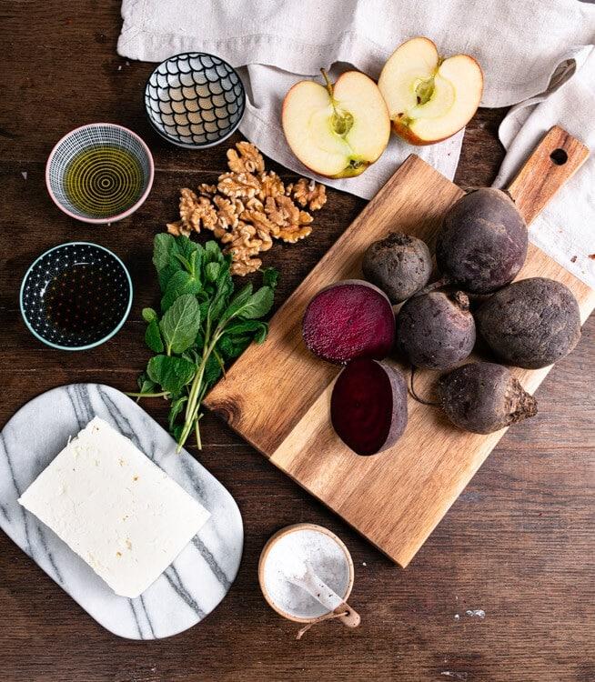 Das Bild zeigt alle Zutaten die für den Rote Beete Salat benötigt werden. Von oben nach unten und rechts nach links sind das ein Apfel. Rote Beete, Walnüsse, Zitronensaft, Olivenöl, Ahornsirup, Minze, Salz und Feta .